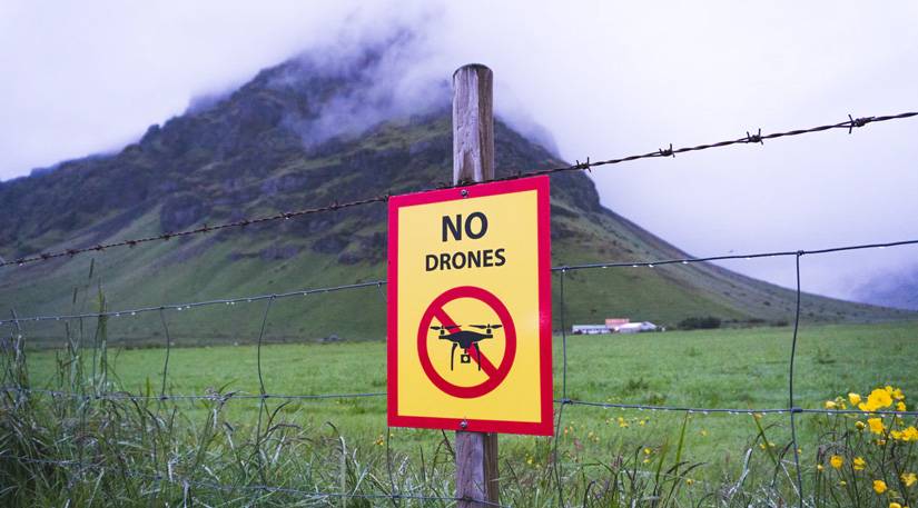 A 'no drones permitted' sign in front of a mountain