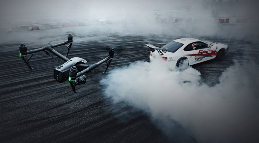 A DJI Inspire 2 drone recording over a race car