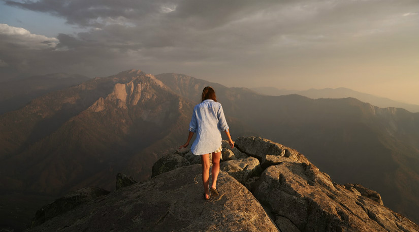 A woman at the top of a mountain