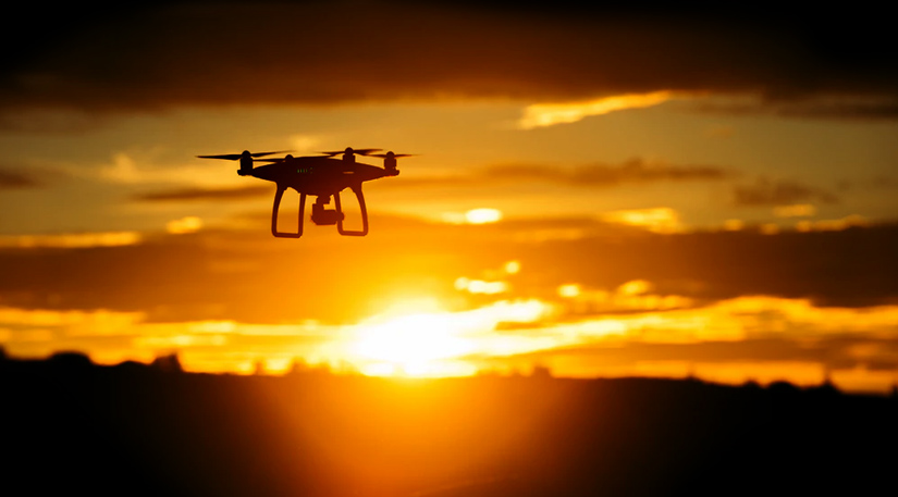 A drone flying into the sunset