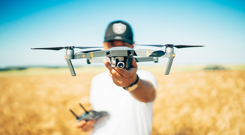 A man holding a drone in a field