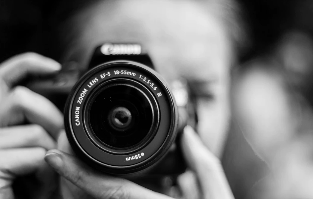 A close up shot of a woman with an SLR camera