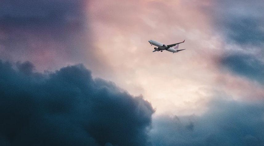 An airplane flying through a colorful sky