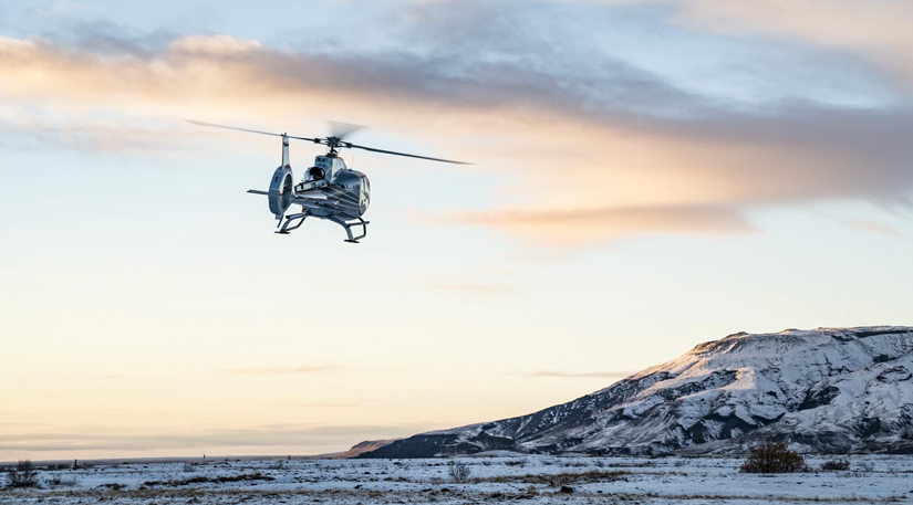 A helicopter flying over an icy tundra