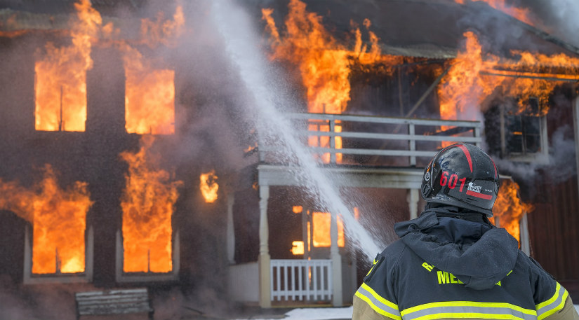 A firefighter fighting a burning building